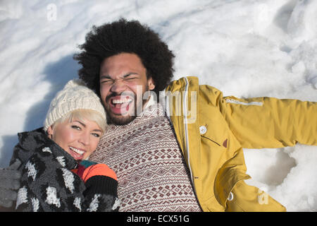 Portrait of happy couple laying in snow - Stock Photo