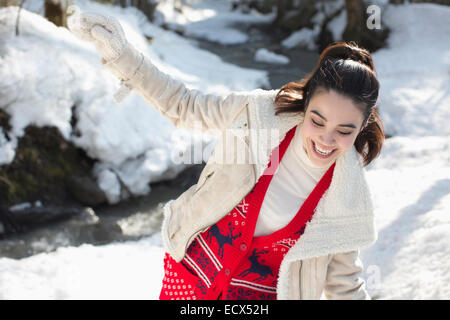 Happy woman playing in snow - Stock Photo