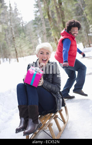 Man pulling woman with gift on sled in snow - Stock Photo