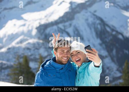 Couple taking selfie in snow - Stock Photo