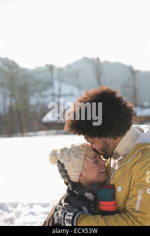 Man kissing woman's forehead in snow Stock Photo