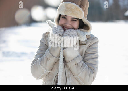 Portrait of smiling woman in snow - Stock Photo