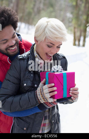 Man surprising woman with Christmas gift in snow - Stock Photo