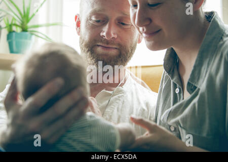 View of parents smiling and holding little baby, sitting beside window - Stock Photo
