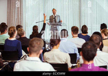 Businessman giving speech in conference room, woman from audience raising hand - Stock Photo