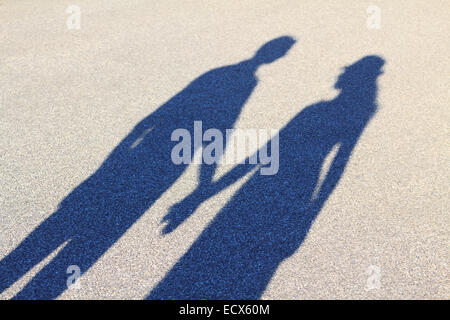 Two lovers cast a long shadow while holdings hands - Stock Photo