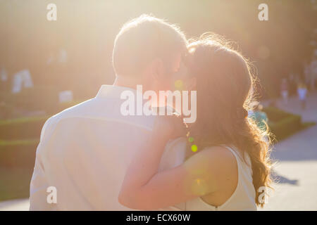 Two lovers - she is whispering something in his ear and he is listening - Stock Photo