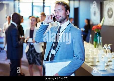 Businessman standing in office, holding document and using mobile phone - Stock Photo