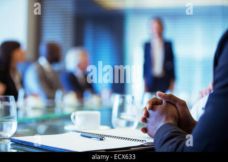 Businessman sitting at conference table in conference room with hands clasped - Stock Photo