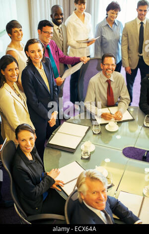 High angle view of smiling business people looking at camera in conference room - Stock Photo