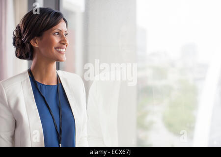 Portrait of smiling mid adult woman looking through window - Stock Photo