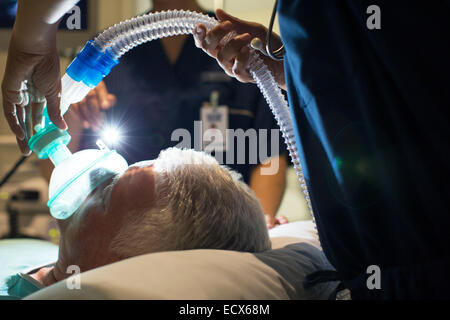 Female doctor wearing mask while anesthetizing elderly patient in surgery - Stock Photo