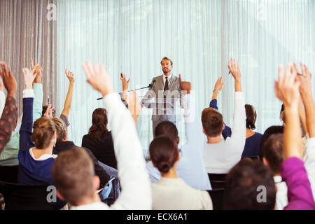 Businessman giving presentation in conference room, people raising hands - Stock Photo