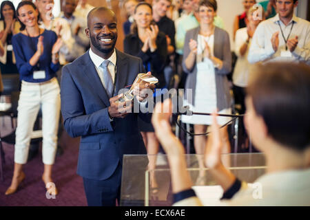 Portrait of young man holding trophy, standing in conference room, smiling to applauding audience - Stock Photo
