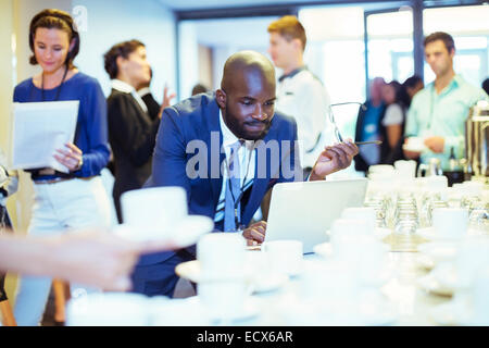 Portrait of businessman using laptop during coffee break at conference - Stock Photo