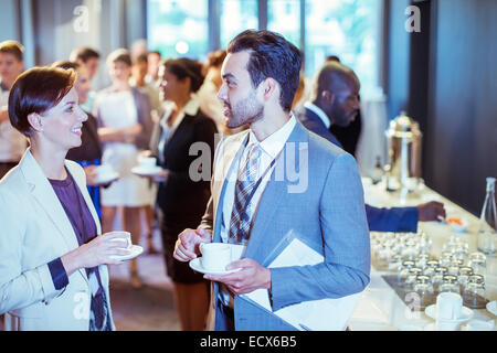 Portrait of man and woman talking in lobby of conference center during coffee break - Stock Photo
