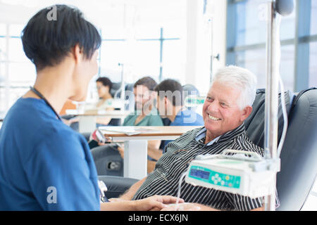 Senior patient undergoing medical treatment talking to doctor in outpatient clinic - Stock Photo