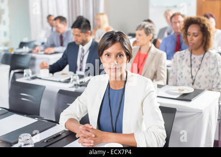 Portrait of woman with group of business people in background attending seminar - Stock Photo