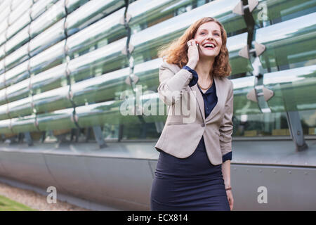 Businesswoman talking on cell phone outdoors - Stock Photo