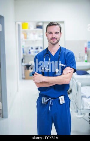Portrait of young male doctor standing in hospital ward with arms crossed - Stock Photo