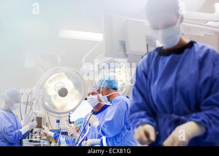 Young nurse preparing medical equipment during surgery - Stock Photo