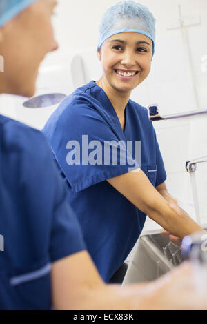 Two female surgeons washing hands in hospital - Stock Photo