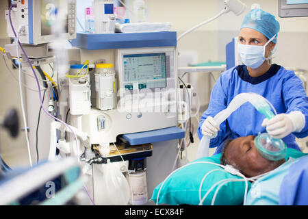 Female doctor wearing surgical clothing anesthetizing patient in operating theater - Stock Photo