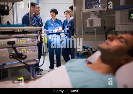 Patient attached to medical monitoring equipment in intensive care unit, doctors standing in doorway - Stock Photo