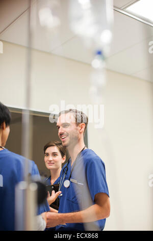IV drip in front of doctors wearing scrubs talking in hospital - Stock Photo