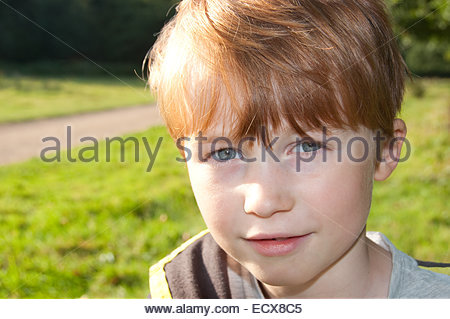 Red headed 8 year old boy, photographed in Norfolk during the summer. - Stock Photo