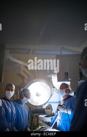 Team of doctors performing laparoscopic surgery in operating theater - Stock Photo