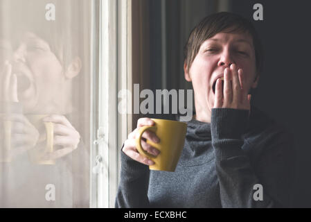 Beautiful sleepy caucasian adult woman drinking cup of coffee and yawning in the early morning. - Stock Photo