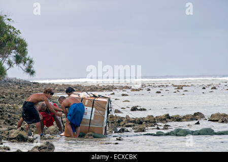 Pacific Islanders retrieve a bundle that air dropped on their island during Operation Christmas Drop December 9, - Stock Photo