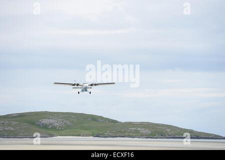 Plane comes into land on the beach at  Eoligarry, Isle of Barra airport. - Stock Photo