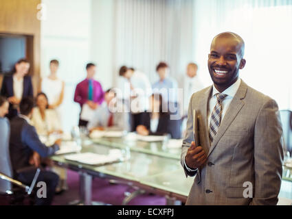 Portrait of smiling young man wearing suit and holding laptop in conference room - Stock Photo