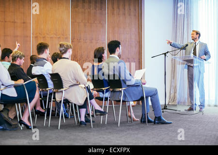 Portrait of businessman standing at transparent lectern talking before audience in conference room - Stock Photo