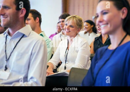 Portrait of smiling woman sitting in conference room, with man and woman in blurred foreground - Stock Photo