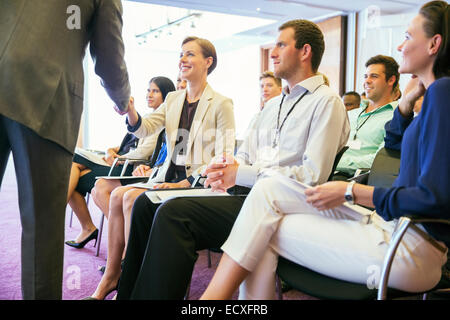 Public speaker shaking hands with people attending seminar - Stock Photo