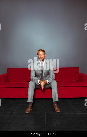 Portrait of businessman wearing grey suit sitting with hands clasped in dark room - Stock Photo