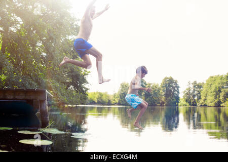 Father and son jumping into lake - Stock Photo