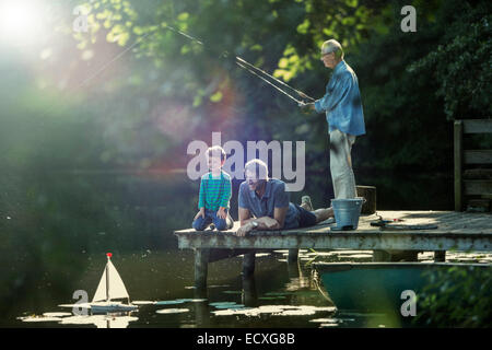 Boy fishing and playing with toy sailboat with father and grandfather at lake - Stock Photo