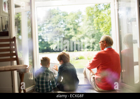 Grandfather and grandsons relaxing in doorway - Stock Photo