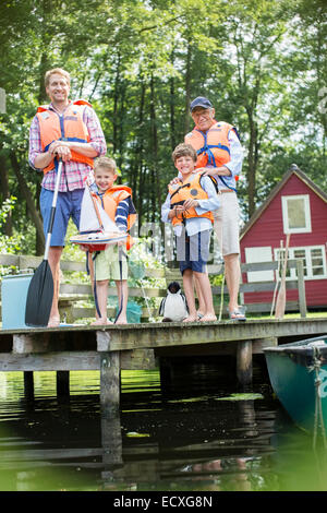 Brothers, father and grandfather wearing life jackets at lake - Stock Photo
