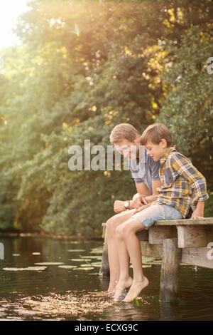 Father and son dangling feet in lake - Stock Photo