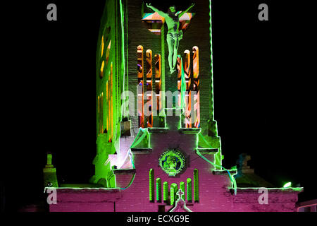 A sculpture of Jesus Christ is seen on a greenly illuminated church bell tower during the annual Festival of Candles - Stock Photo