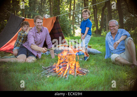 Boy, father and grandfather relaxing near campfire - Stock Photo