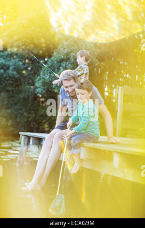 Father and sons fishing from dock - Stock Photo