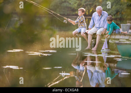 Grandfather and grandsons fishing and playing with toy sailboat at lake - Stock Photo