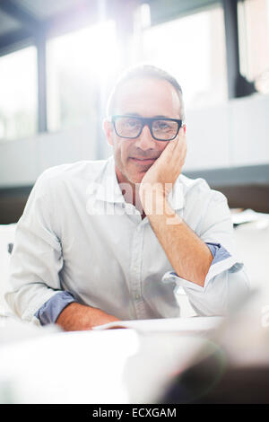 Smiling older man sitting at desk - Stock Photo
