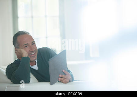 Older man using digital tablet on sofa - Stock Photo